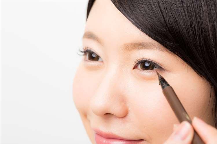 صورة لامرأة ترسم خط عين